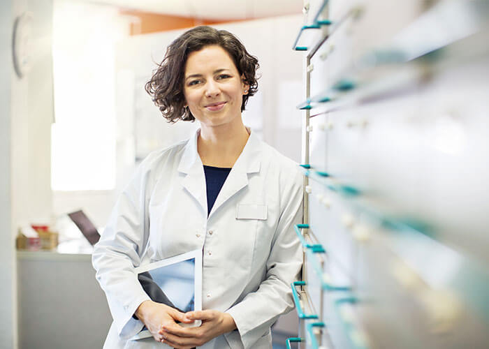 Pharmacist leaning against cabinet holding files.